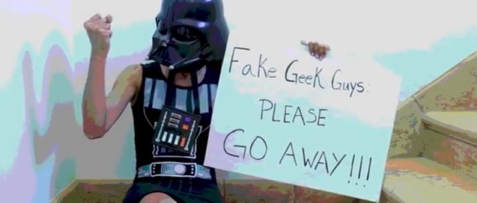Auf einer Treppe sitzt eine weiße Person mit Darth Vader-Maske und einem ärmellosen Top im gleichen Stil. Die rechte Faust ist geballt, die Linke hält ein Plakat: Fake Geek Guys: PLEASE GO AWAY!!!