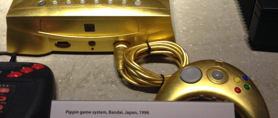 Ein flacher Rechner, Pippin von Apple, in gold sowie ein angeschlossener goldener Controller liegen auf einem Tisch.