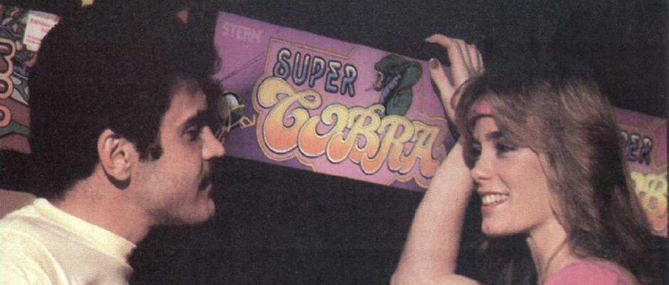"""Ausschnitt aus dem Titelbild des Magazins Vidiot: Ein Mann mit dunklelm Schnurrbart und eine junge Frau mit Stirnband lehnen an einem Arcadeautomate """"Super Cobra"""""""