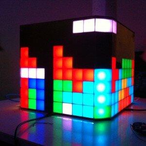 Vor dunklen Hintergrund steht ein schwarzer Würfel auf dessen Seiten ein Tetrisspiel in bunten Farben leuchtet. Über vier leeren Plätzen schwebt ein langes 4-Stück…