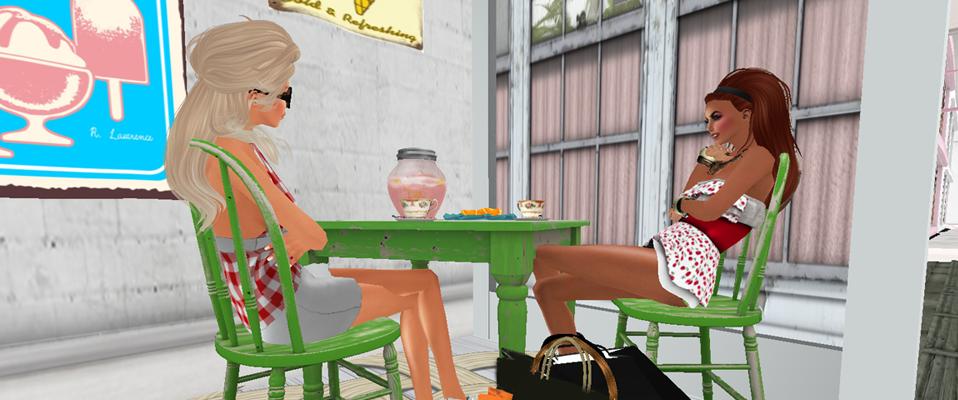 An einem grünen Tisch sitzen eine weiße Frau und eine schwarze Frau in kurzen Kleidchen.