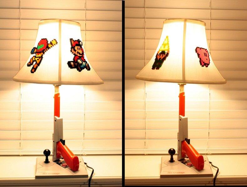 Eine weiße Lampe, der Fuß besteht aus einem NES Advantage Joyboard und einer Zapper-Lightgun. Auf dem Schirm sind Bügelperlenbilder, etwa Mario.