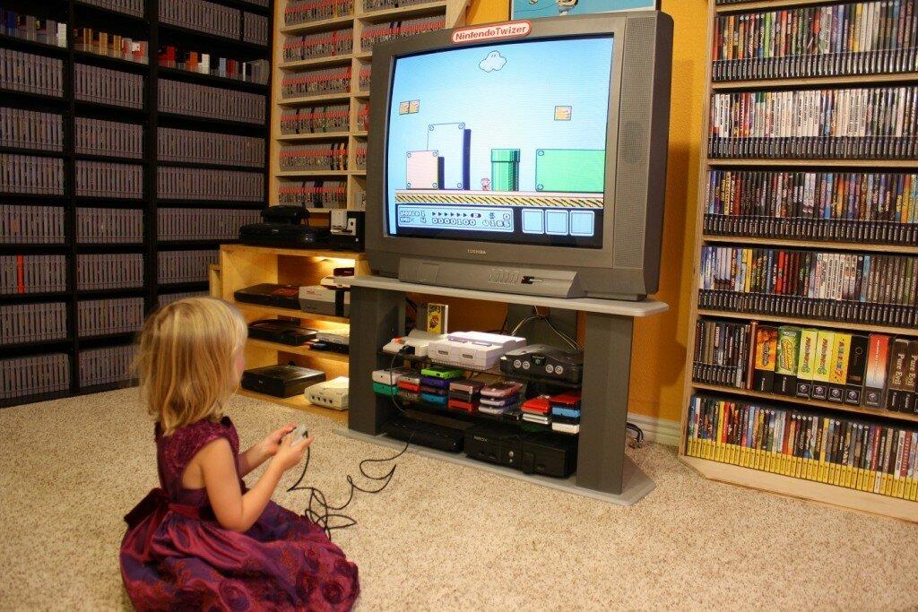 Vor Regalen mit sehr vielen Spielen und einem Fernseher sitzt ein blondes Mädchen und spielt Super Mario