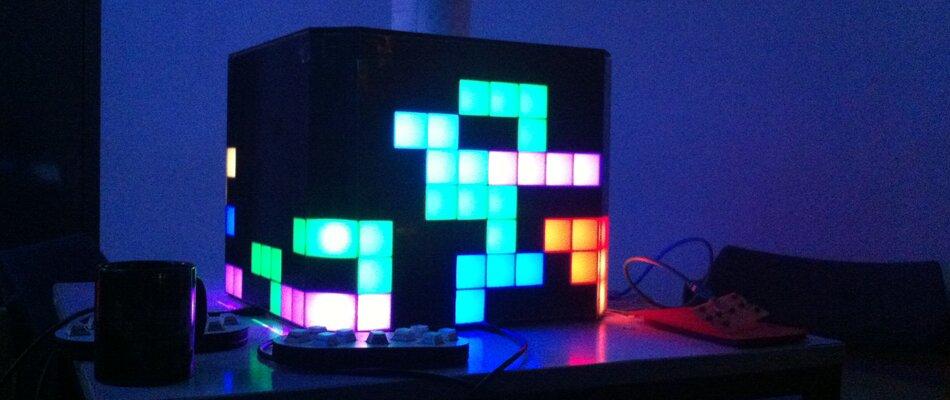 Vor dunklen Hintergrund steht ein schwarzer Würfel auf dessen Seiten ein Tetrisspiel in bunten Farben leuchtet.
