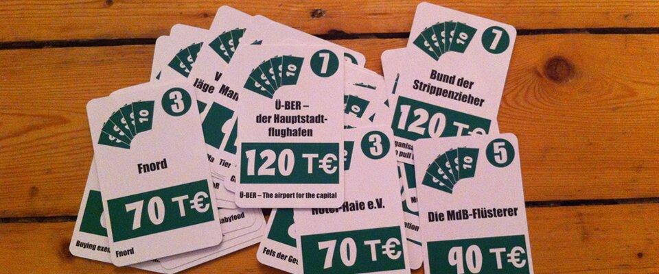 """Auf Holz liegen Spielkarten in grün mit Stimmsummen und Slogans: """"Fnord"""", """"Ü-BER – Der Hauptstadtflughafen"""" – """"Hotel-Haie. e.V."""" – """"Bund der Strippenzieher"""" – """"Die MdB-Flüsterer"""""""