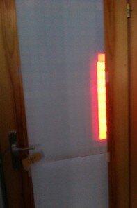 """Die Glasfläche einer hellen Tür ist weiß abgeklebt. Darauf leuchten in rot 10 """"Pixel"""" hintereinander."""