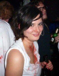 Eine weiße Frau mit schwarzen Haaren und Blut auf ihrem weißen Shirt.