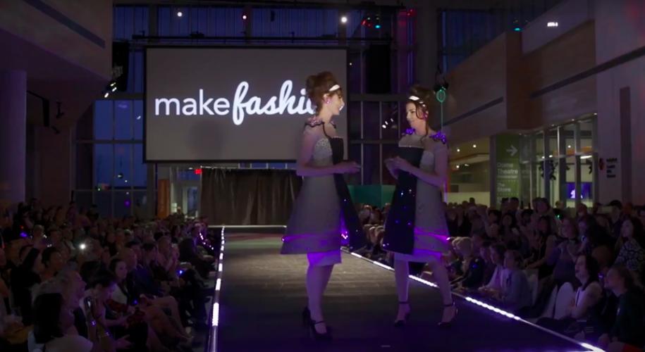 Zwei Frauen stehen auf einem Laufsteg und halten Smartphones in der Hand. Ihre hellen Kleider haben einen lila leuchtenden Abschluss und vorne ein schwarzes Display mit bunten LEDs.